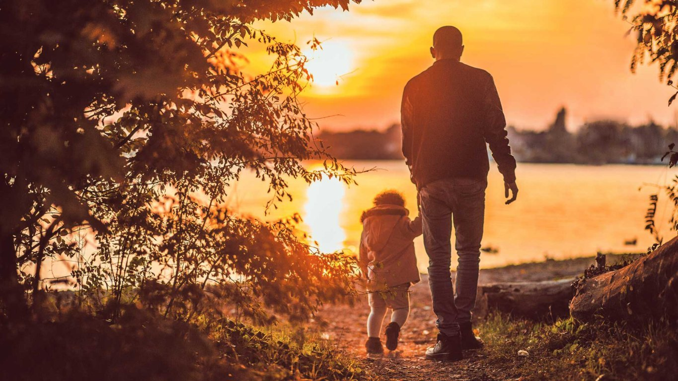 sundown father and daughter holding hands walking