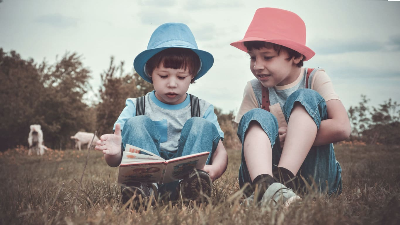 little boy with blue hat and little boy with red hat